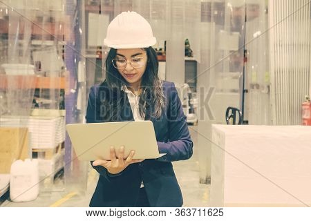 Focused Manager In Hard Hat Using Laptop At Factory. Front View Of Concentrated Asian Employee Holdi