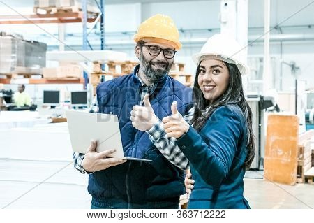 Smiling Factory Workers Showing Thumbs Up. Front View Of Cheerful Employees Posing With Laptop At Ma