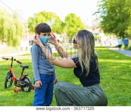 Mother And Child In The Open Air Wear Facemask During Coronavirus And Flu Outbreak. Virus And Illnes