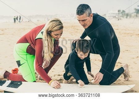 Happy Family Waxing Surfboard On Beach. Mother, Father And Little Son In Wetsuits Sitting On Sand An