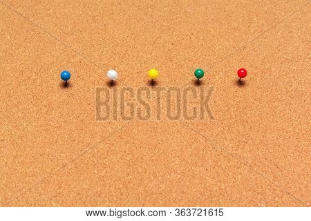 Colorful Thumbtacks Pinned On A Cork Board Close Up