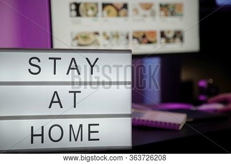 A Lightbox With The Text Stay At Home, A Person Working At A Computer In A Neon Light On The Backgro