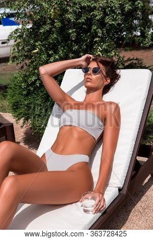 A Beautiful Woman With A Perfect Slim Figure In A Bikini Swimsuit Is Relaxing On A Sunbed By Hotels