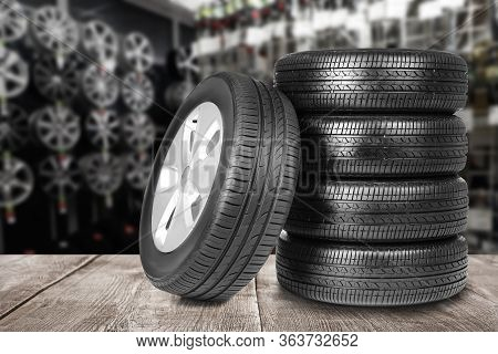 Car Tires On Grey Wooden Surface In Auto Store