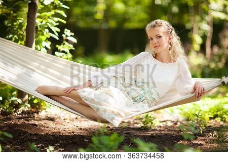 Front View Of Beautiful Young Woman Resting On Hanging Hammock Swing Bed In Spring Forest. Charming