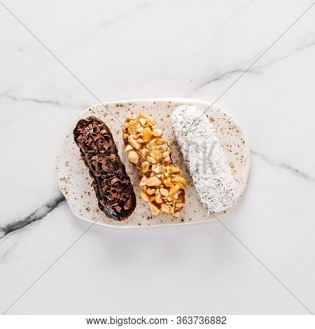 Set Of Three Homemade Eclairs On Marble Background. Top View Of Delicious Healthy Profitroles With D