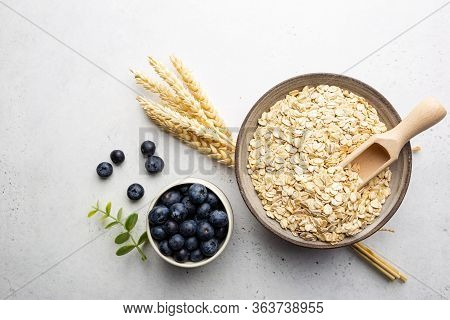 Rolled Oats Or Oat Flakes In Bowl And Wooden Spoon On White Table, Top View With Copy Space