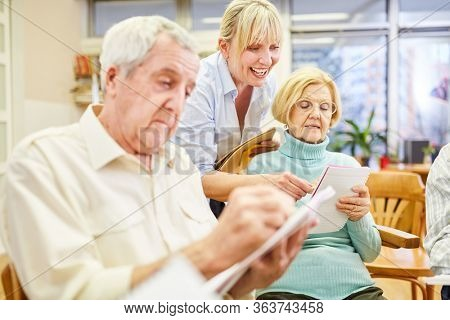 A doctor or therapist supports senior citizens in group therapy when writing