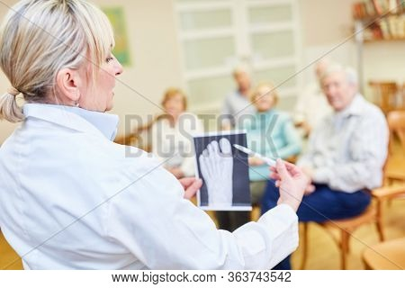 Doctor gives a lecture on health and foot care in a retirement home