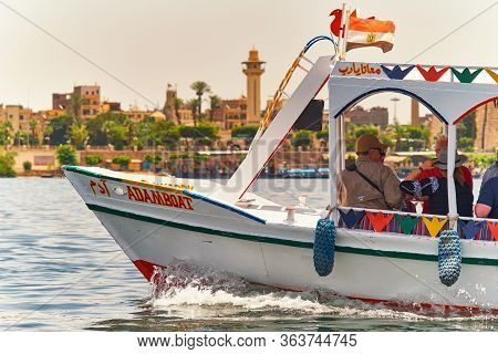 Luxor / Egypt - May 23 2019: Tourist Riverboat Cruising On The Nile In Luxor, With Luxor Temple In T
