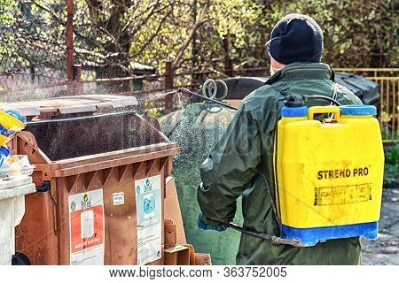 Ruzomberok, Slovakia - April 29, 2020: Cleaning And Disinfecting Coronavirus On Trash Cans  By Man I