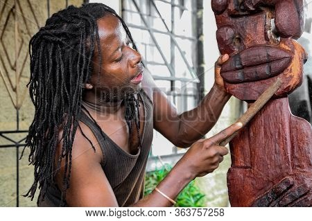 African Man Sculptor Carving A Traditional Statue Out Of Wood