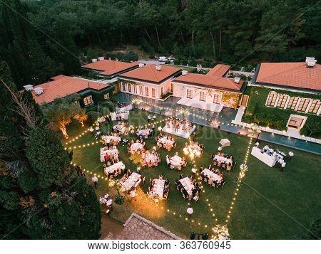 Budva, Montenegro - 10 June 2019: Wedding Banquet, Dinner, At Dusk Under The Light Of Garlands. Tabl