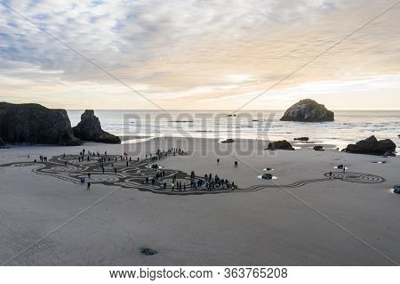Bandon By The Sea, Oregon / Usa - March 08 2020: People At Sunset Walking Through A Labyrinth On The