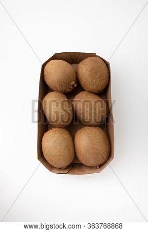 Whole Brown Kiwi Fruits In Carton Box. Hairy Fresh Ripe Kiwifruits. Closeup, Top View. Fresh Vegetab