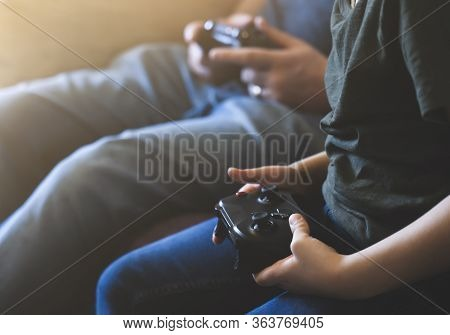 Hands Holding Video Game Or Game Console. Child Boy And Father Playing Game Online Stay At Home Whil
