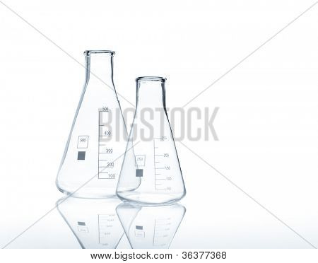 Two empty conical Erlenmeyer flasks with reflection on the surface of the table, isolated
