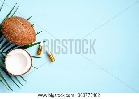 Coconut Oil With Half Of Coconut And Palm Leaf On Blue Background. Flat Lay, Top View. Spa Natural O