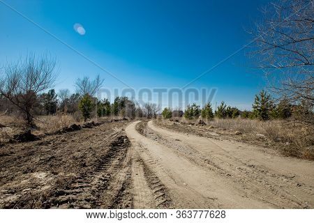 Grader Rural Road Leading To The Village. Dirt Mud And Dusty Road Through A Field And Trees Against