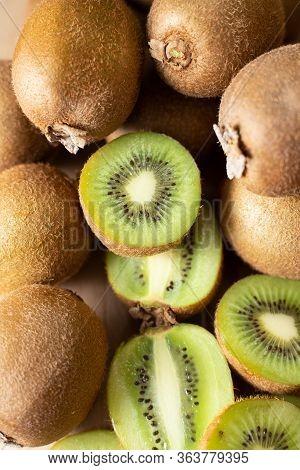 Ripe Juicy Kiwi Fruits Closeup. Whole And Cut Half Of Kiwifruits. Vertical Shot, Top View. Healthy O