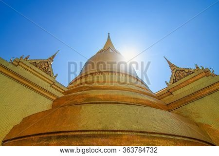 Beautiful Temple And Golden Stupa Complex With Lens Flare Against Blue Sky In Grand Palace, Bangkok