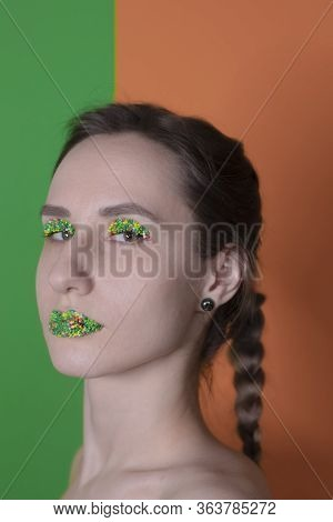 Young woman portrait with a candy makeup - multicoloured pastry topping pearls on her lips and eyeli