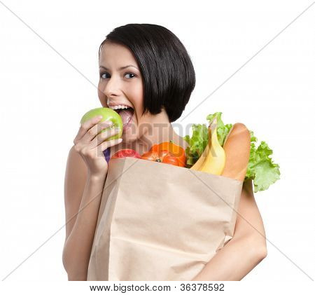 Lovely girl eats a green apple, keeping the packet full of healthy food, isolated, white background