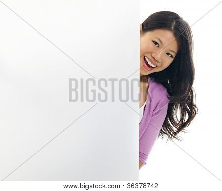 Cheerful young Asian woman hiding on a blank space.