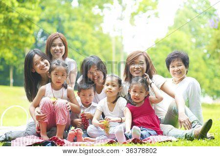 Happy Asian family enjoying picnic at outdoor park