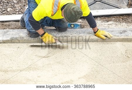 Workman In Safety Jacket Preparing The Foundation Of Patio Pavers By Smoothing The Sand With Trowels