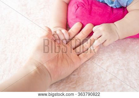 Asian Female Hand Holding  Newborn Baby Hand. Mom With Her Child. Maternity, Family, Birth Concept.