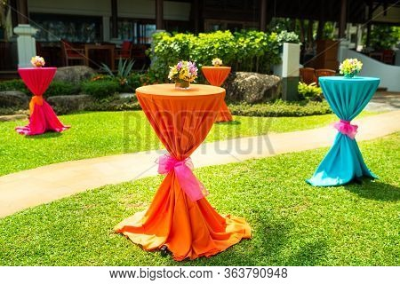 Colorful Beautiful Orchid Bouquet Decor In Glass Vase Setup On Wooden Dinner Table In India Wedding