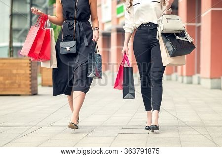 Low Angle Shot Of Two Girls Walking Near Shopping Center Together Carrying Colorful Paperbags After