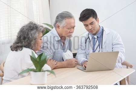Caucasian Doctor Use Laptop And Talk With Old Asian Male Patient About Disease Symptom, Elderly Heal