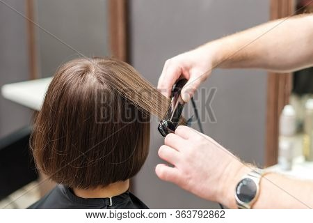 Professional Hairdresser Straightening Brown Hair With Hair Straighteners In Beauty Salon, Concept B