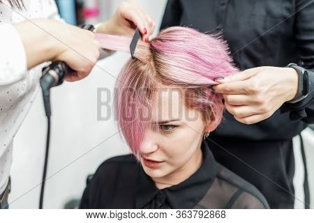 Professional Hairdresser Straightening Pink Hair With Hair Straighteners In Beauty Salon, Concept Ba