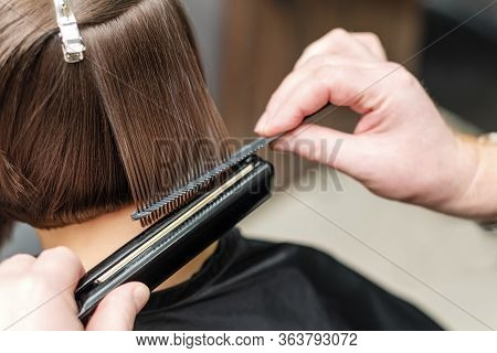 Professional Hairdresser Straightening Short Brown Hair With Hair Straighteners In Beauty Salon, Con