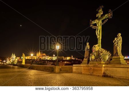Panoramic View Of Prague Skyline At Night. Statuary Of The St. Cross With Calvary And Gas Lamps On T