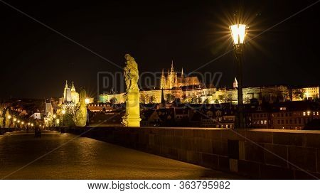 Panoramic View Of Prague Skyline At Night. Statues And Gas Lamps On The Charles Bridge And Prague Ca