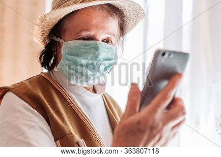 Elderly Woman In Isolation Wearing A Medical Mask, Talking On The Mobile Phone, Video Call. Quaranti