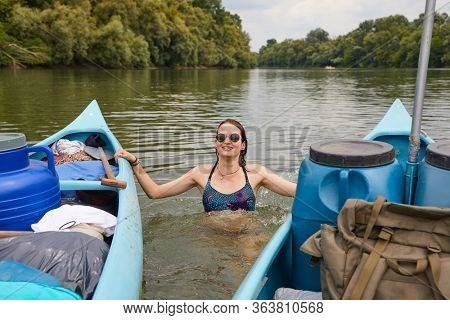 Canoeing, swimming in the river, grabbing the front of the boat