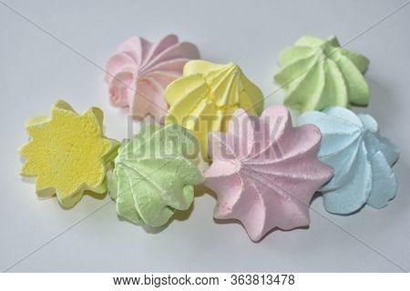 Multicolored Meringue Pieces On A White Background. Multicolored Meringue Pieces On A White Backgrou