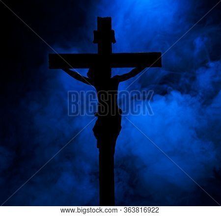 A Small Statue Of Jesus Christ On The Cross, In Silhouette, Against A Smoky Background