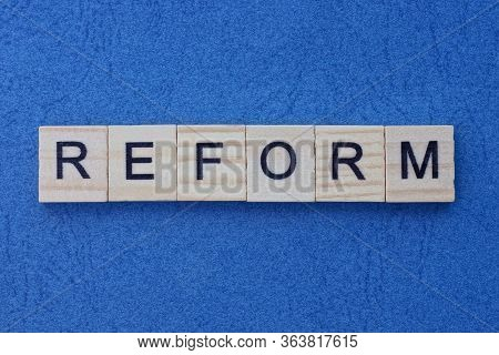Text On Gray Word Reform Of Small Wooden  Letters Lies On A Blue  Table