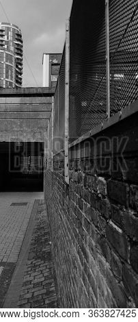 Wall on a empty alley way, leading to a dark stairway, in London's east end. Taken in black and white.
