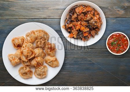 Dumplings On A White Plate On Blue Wooden Background. Dumplings In Tomato Sauce With Salad. Dumpling