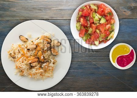 Rice With Mussels And Carrots On A White Plate. Rice With Mussels And Carrots On A Blue Wooden Backg