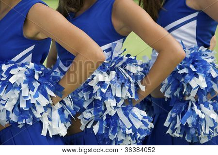 Midsection of young female cheerleaders holding pom-poms