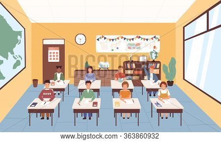Smiling Pupils Sitting At Desks In Classroom. Geography Room Interior. Children Listening Lecture At