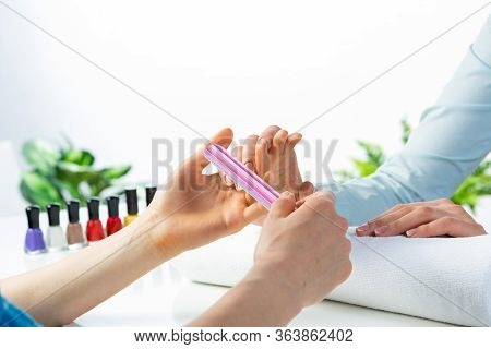 Manicurist Using Nail File And Create Perfect Nails Shape. Closeup Of Female Hand Preparing For Appl